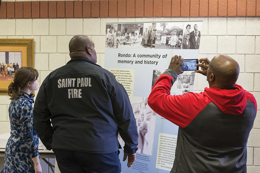 Three people face away from the camera reading a tall placard called 'Rondo: A community of memory and history.' Gerone Hamilton's jacket says 'Saint Paul Fire.