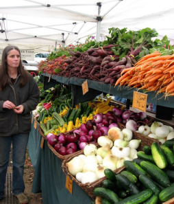 A woman looks on at the large two-tier display of produce underneath an expansive pop-up tent.