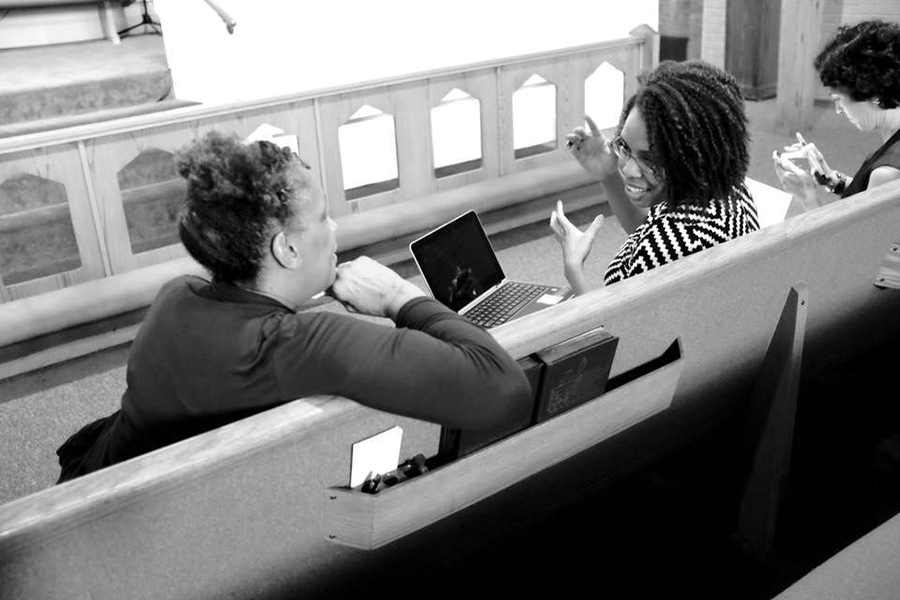 Murrain and participant are sitting on a church pew while they have a discussion. Murrain has her laptop in her lap.