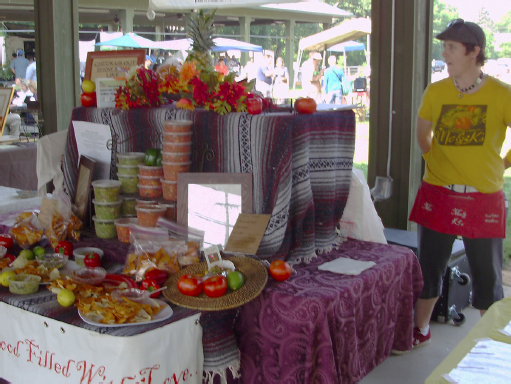 Stacks of salsa and tropical fruit on display. Samples of the salsa sit in front. A woman stands behind the display.