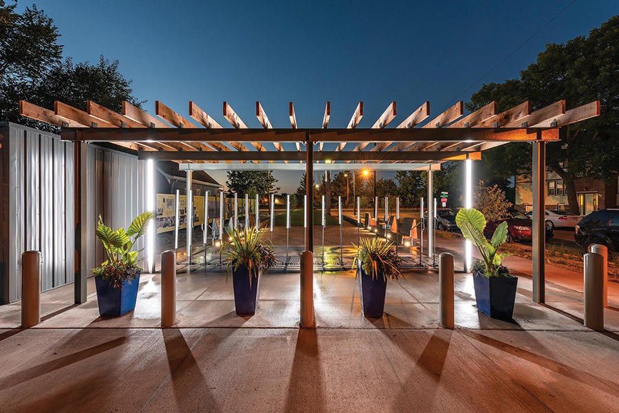 Nighttime view of the Rondo Plaza. The lights illuminate the art installation underneath a wooden pergola. Four large, blue planters are placed equal distance apart in front of the pergola.
