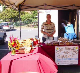 "Woman stands behind her canopy stall. On it a sign reads, ""Country Rhodes Produce and Bakery."""
