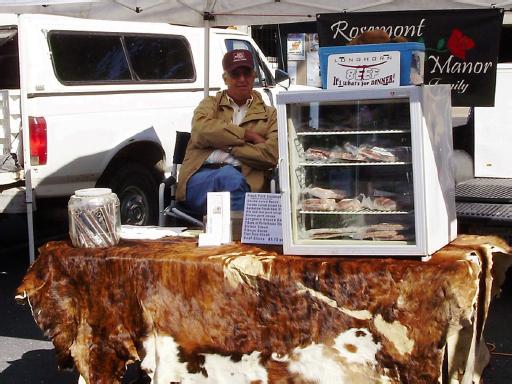 "A man with his arms crossed, sits behind a cow skin covered stall. On the stall is a cooler filled with packed meats and a sign that reads, ""Longhorn Beef Stall – It's what's for dinner!"""