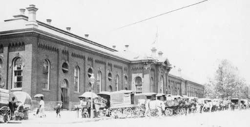 View from 7th Street circa 1914. Many carriages/buggies are parked in front of a large building.