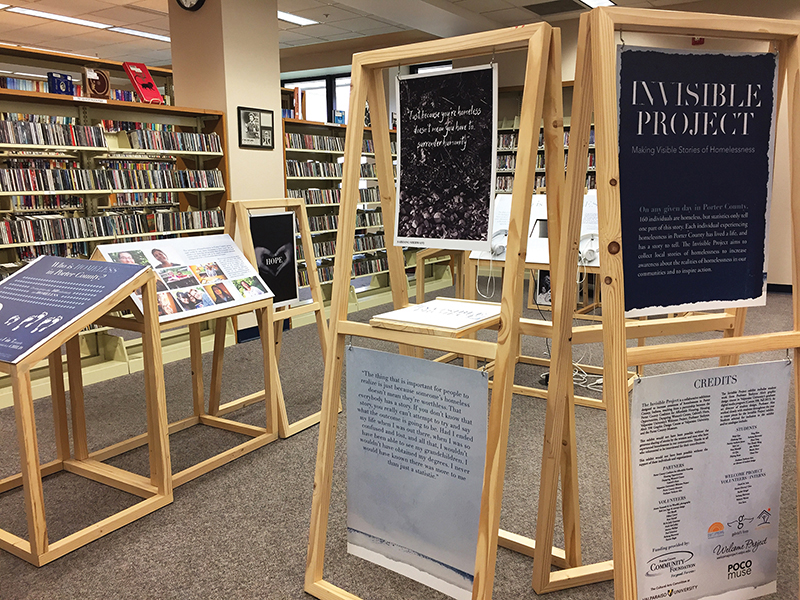 Wooden structures of the Invisible Project exhibit installed in a library.
