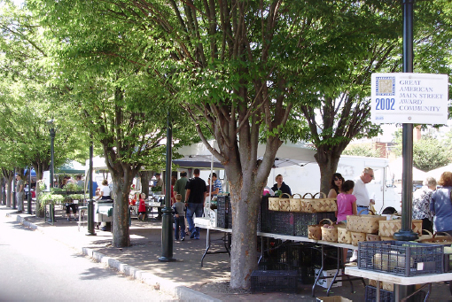 Entrance to the market includes tables underneath trees and set up along the sidewalk.