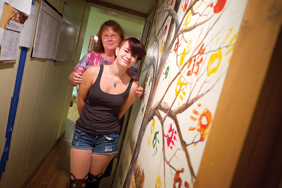 Mother holds teenage daughter in hallway next to tree mural.