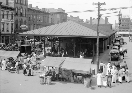 Horse and buggies line the street in this view of Findlay Market from Race Street (circa 1930).