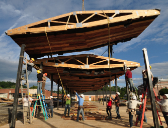 Pavilion is wood. One piece is being hoisted into place by a crew of workers.