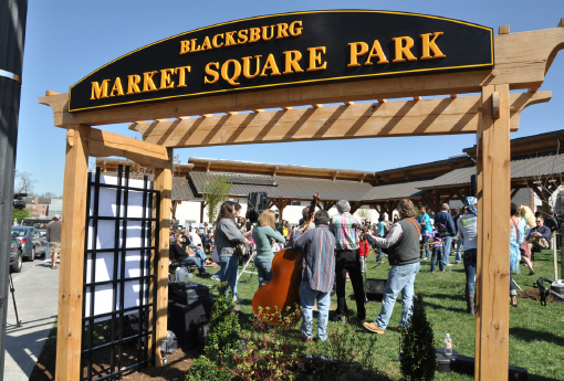 "Crowds gather on the lawn underneath a sign that reads, ""Blacksburg Market Square Park"" on Market day."