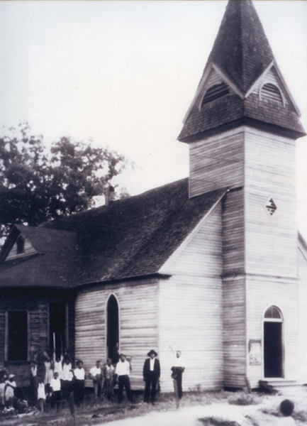 This historic photograph depicts a dozen or more congregants standing to the left of the church. The church is wooden with a single, large room and a tall bell tower in the front.