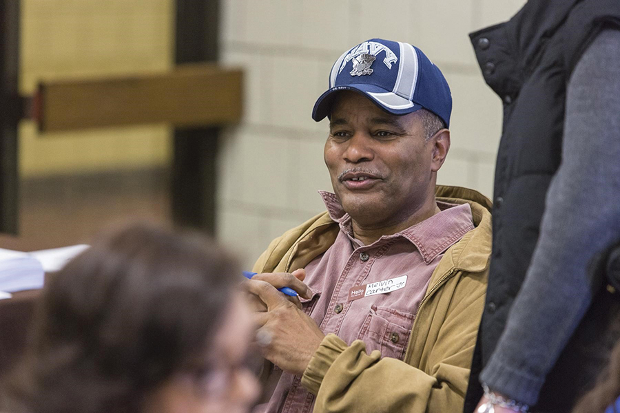 Melvin Carter, Jr. smiles during a conversation. He's wearing a blue hat, a pink button-down shirt, and a tan jacket. A couple other figures surround him but are out of focus.
