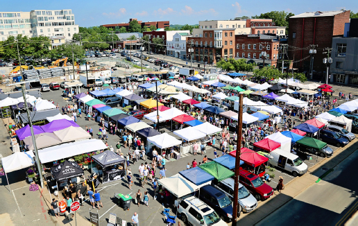 Aerial view of the market. Over 50 vendor stalls with large crowds moving around the market. Bright and sunny outside.