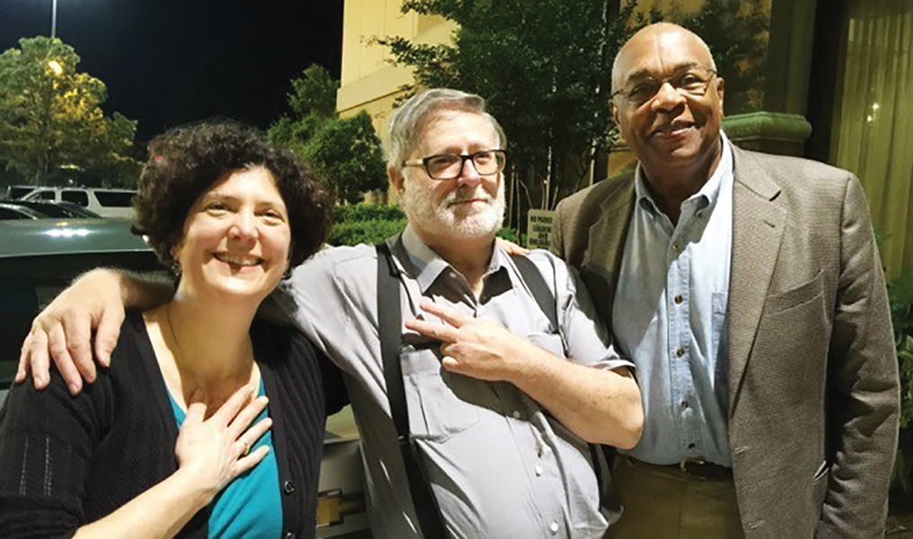 Naomi Nelson, Bruce Hartford, and Courtland Cox gather together for a photo. Bruce has his arm around Naomi's shoulder.