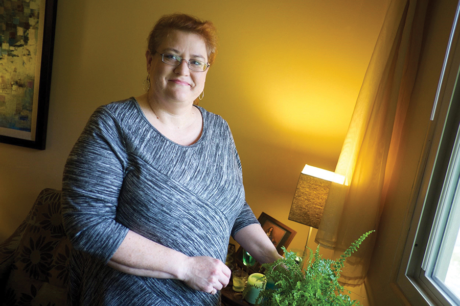Smiling woman in warmly lit room tending a house plant.