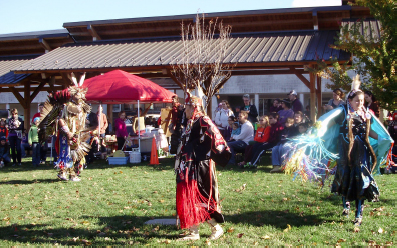 Native Americans dressed in traditional attire performing dances on a green space at the market. A pavilion and a small pop-up tent are behind them.