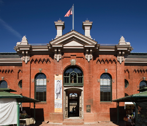 Eastern Market entrance showing brick detailing and large windows. An American flag sits atop the building.
