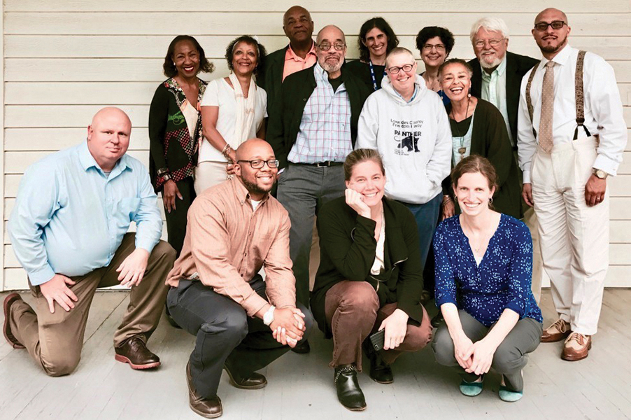 14 SNCC project partners pose for a photo on the porch at the Center for Documentary Studies.