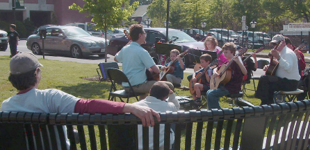 Renaissance Music Academy musicians play at the farmers market. A man sits on a bench listening.