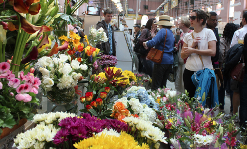 People stand around admiring Blue Iris Flowers stall. Flower bouquets of different colors and sizes on are display.