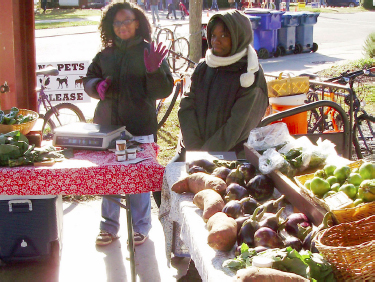 Two young girls sell produce at their stall and wave to guests.