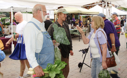 Market goers standing underneath pop up tents, holding produce and talking. A man in overalls holding up radishes and kale.