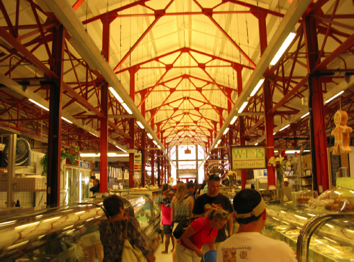 Inside Findlay market. Distinctive Tuscan red Fink trusses line the ceiling with patrons milling around below.