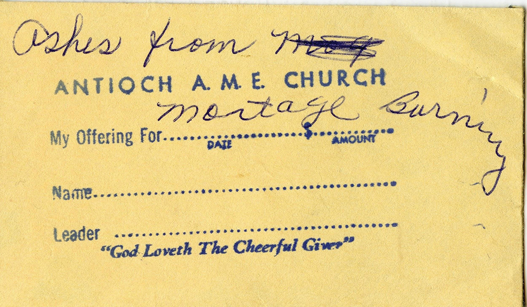 A close-up photograph of the envelope holding the ashes from the mortgage burning ceremony. The envelope is an old collections envelope with a stamp for date, name, and leader, with the words 'God Loveth The Cheerful Giver.