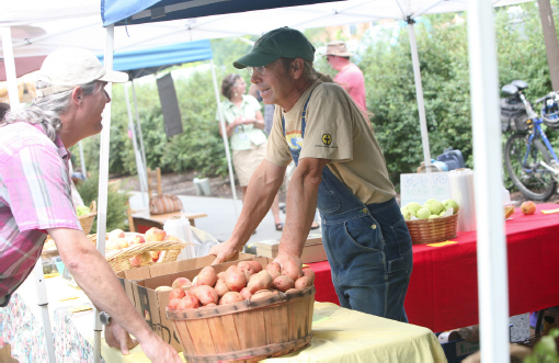 A patron conversing with farmer Dennis Dove over baskets of produce.