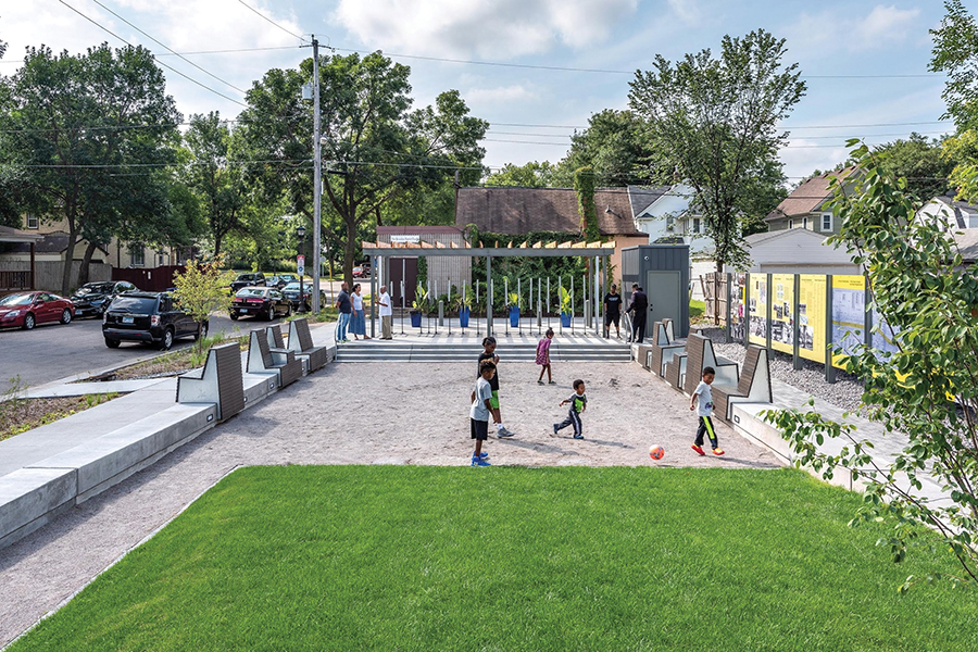 A daytime view of the commemorative plaza. In the center of the photograph, five kids are playing with a soccer ball on the dirt and grass. Along the right side, the wall of panels depicting the history stand out in bold yellow. In the background, a couple groups of adults are talking next to the art installation by Seitu Jones.