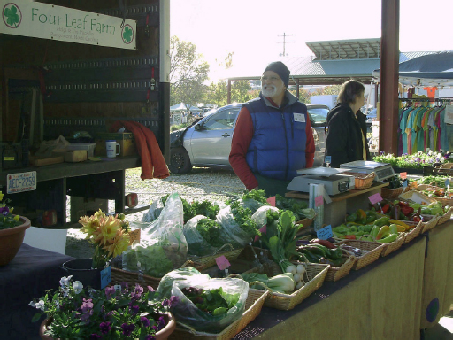 A man in a blue vest jacket stands behind the Four Leaf Farm's stall, which has a wide variety of produce atop it.